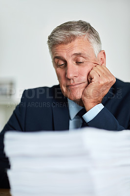 Buy stock photo Cropped shot of a mature businessman looking bored at work