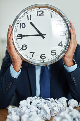 Buy stock photo Shot of an unrecognizable businessman holding a large clock in front of his face