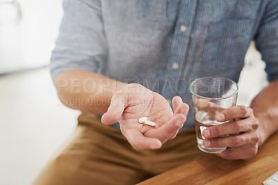 Buy stock photo Closeup shot of an unrecognisable man holding a glass of water and medication in his hands