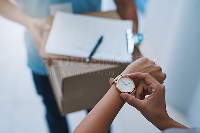 Buy stock photo Cropped shot of an unidentifiable businesswoman checking the time on her watch as the courier arrives with a delivery