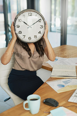 Buy stock photo Shot of an unidentifiable businesswoman holding a clock in front of her face while sitting at her desk
