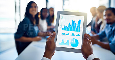 Buy stock photo Shot of an unidentifiable businessman holding up a tablet while sitting in a meeting with his colleagues