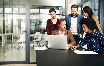 Buy stock photo Shot of a group of colleagues using a laptop together at work
