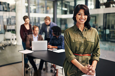 Buy stock photo Portrait of a confident young woman standing in a modern office with her colleagues in the background