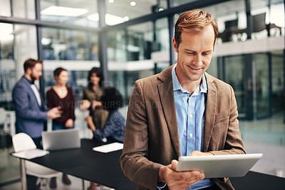 Buy stock photo Shot of a businessman using a digital tablet during a meeting at work