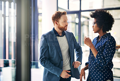 Buy stock photo Shot of two colleagues having a discussion in a modern office