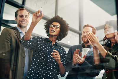 Buy stock photo Shot of colleagues having a brainstorming session on a glass wall at work