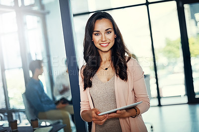 Buy stock photo Portrait of a confident young businesswoman using a digital tablet in an office