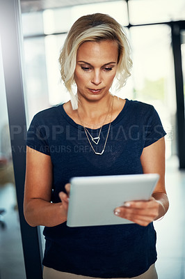 Buy stock photo Cropped shot of a young businesswoman using a digital tablet in an office