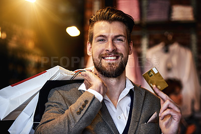 Buy stock photo Shot of a man holding up his credit card while out shopping