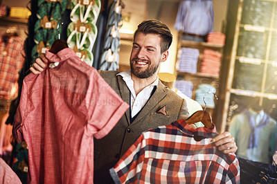 Buy stock photo Shot of a young man looking at clothing in a shop