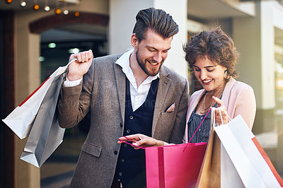 Buy stock photo Shot of a woman showing her boyfriend what she bought while out shopping