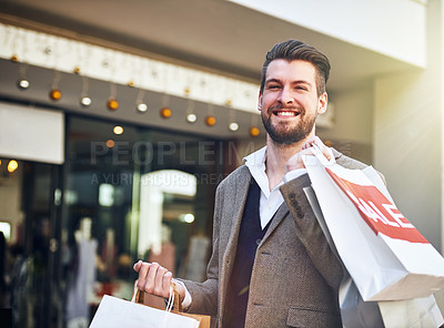 Buy stock photo Cropped shot of a young man carrying shopping bags