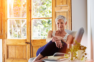 Buy stock photo Portrait of a smiling mature woman relaxing on a chair at home