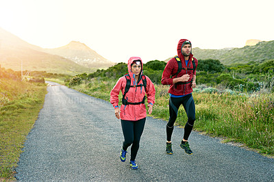 Buy stock photo Shot of two friends out for a run together on a cool morning