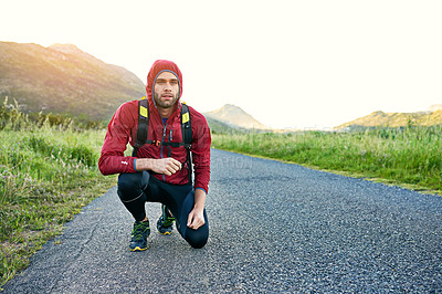 Buy stock photo Shot of a focused young man crouching while preparing for a run on a cool morning