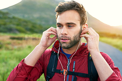 Buy stock photo Shot of a focused young man putting on headphones while preparing for a morning run