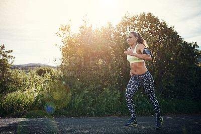 Buy stock photo Shot of a focused young woman out for a run in the early morning