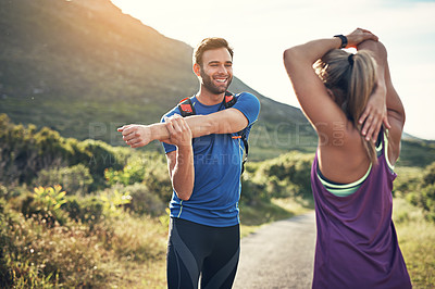 Buy stock photo Shot of two friends stretching before an early morning run