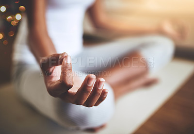 Buy stock photo Cropped shot of an unrecognizable young woman practicing yoga indoors
