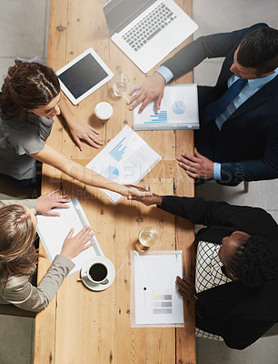 Buy stock photo High angle shot of a group of businesspeople shaking hands during a meeting in an office