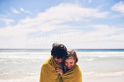 Buy stock photo Cropped shot of an affectionate young couple wrapped in a blanket on the beach