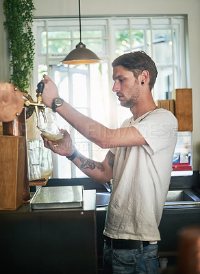 Buy stock photo Shot of a young bartender pouring beer from a tap behind the bar