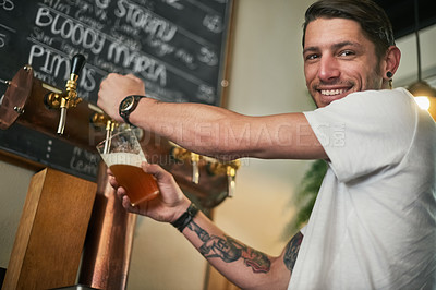 Buy stock photo Portrait of a young bartender pouring beer from a tap behind the bar