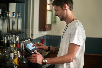 Buy stock photo Shot of a young bartender entering an order on a point of sale system behind the bar