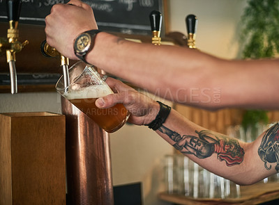 Buy stock photo Cropped shot of an unidentifiable young bartender pouring beer from a tap behind the bar