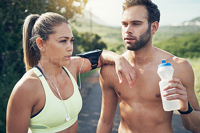 Buy stock photo Shot of two young friends drinking water while taking a break from an early morning run
