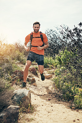 Buy stock photo Shot of a focused young man running alone outside on a trail