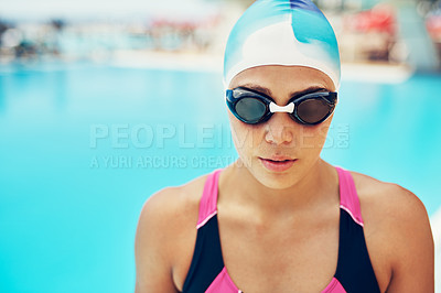 Buy stock photo Portrait of an athletic young woman in swimming goggles standing by the edge of a swimming pool