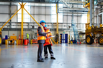 Buy stock photo Shot of two warehouse workers talking together over a clipboard inside of a large warehouse