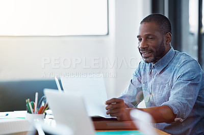 Buy stock photo Shot of a smiling man sitting at his desk in an office reading paperwork