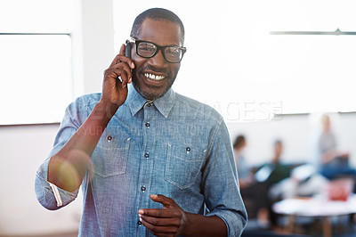 Buy stock photo Portrait of a smiling man standing in an office talking on a cellphone