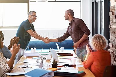 Buy stock photo Shot of two colleagues shaking hands together over a boardroom table while colleagues look on