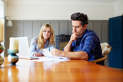 Buy stock photo Shot of a concerned looking young couple sitting together at their kitchen table paying bills online