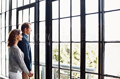 Buy stock photo Shot of an affectionate mature couple standing together in front of a window at home