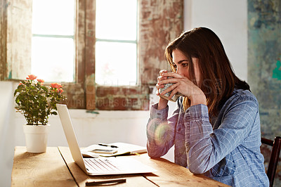 Buy stock photo Shot of a young woman drinking a coffee while sitting at a desk in her room using a computer