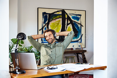 Buy stock photo Shot of a young man sitting at home with his hands behind his head wearing headphones and working on a laptop