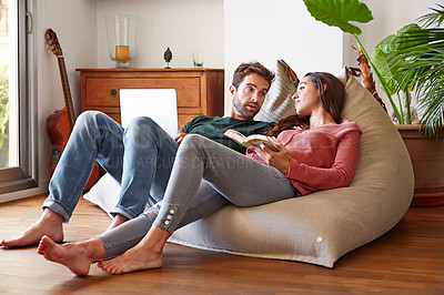Buy stock photo Shot of a smiling young couple talking together while relaxing on a beanbag sofa at home