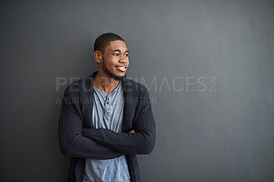 Buy stock photo Shot of a smiling young man standing with his arms crossed against a gray wall
