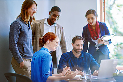 Buy stock photo Shot of a group of colleagues talking together over a laptop on a desk in an office