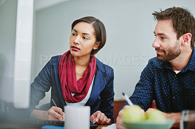 Buy stock photo Shot of two colleagues talking together while sitting at a desk in an office