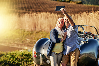 Buy stock photo Shot of a senior couple posing for a selfie while out on a roadtrip in a convertible