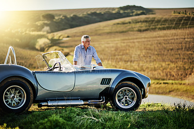 Buy stock photo Shot of a senior man looking at a map while out on a roadtrip in a convertible