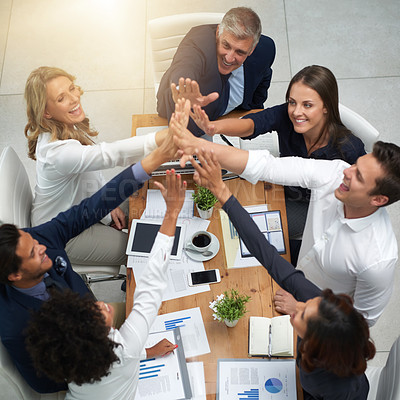 Buy stock photo High angle shot of a group of businesspeople high fiving together in an office