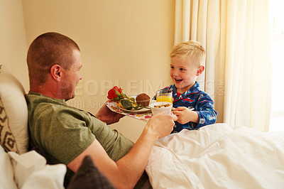 Buy stock photo Cropped shot of a little boy serving breakfast in bed to his father at home