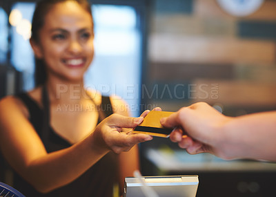 Buy stock photo Shot of a young barista accepting payment from a customer in a coffee shop